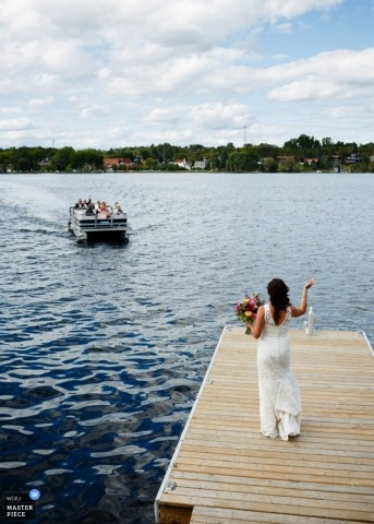 Toronto wedding photographer captured this photo of the bride standing on the dock as a boat approaches with guests and bridal party