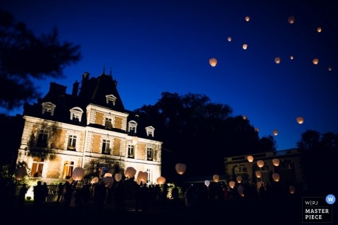 Paris gets a shot of the outside of a beautiful house at night while wedding guests release white paper lanterns into the deep blue sky