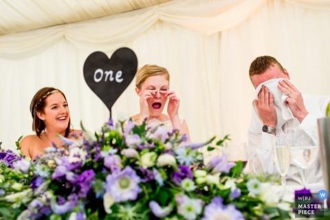 De trouwfotograaf van Devon creëerde dit emotionele beeld van de bruid en bruidegom die tranen afvegen terwijl ze luisteren naar toespraken tijdens de receptie aan tafels die zijn versierd met paarse bloemstukken