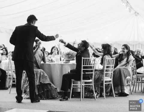 Gloucestershire wedding photographer captured this black and white photo of the groom toasting during the wedding reception