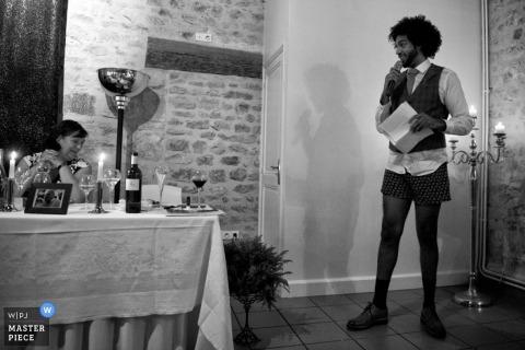 Fotograf ślubny Lot-et-Garonne uchwycił czarno-biały obraz pana młodego wygłaszającego przemowę w bokserkach na przyjęciu