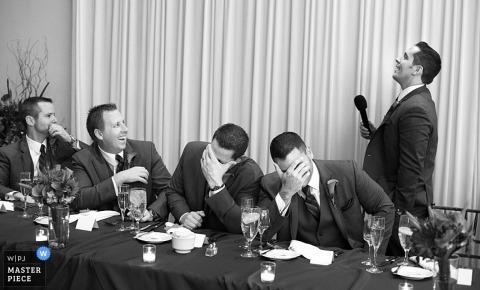 Il fotografo di matrimoni di Chicago ha catturato questa foto in bianco e nero degli groomsmen che reagiscono al discorso esilarante dei migliori mans alla reception