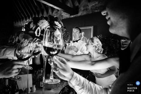 Die Braut und die Gäste greifen über den Tisch zu einem Toast in diesem Schwarzweißbild, das von einem Hochzeitsfotografen aus Guernsey auf den Kanalinseln aufgenommen wurde.
