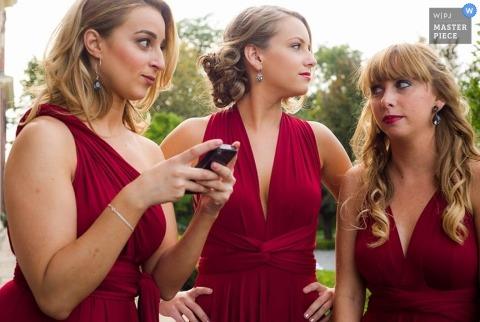 Un photographe de mariage de Chicago prend la photo d'un groupe de demoiselles d'honneur vêtues de robes rouges qui discutent avant la cérémonie