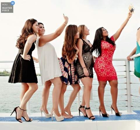 Key West wedding photographer makes a picture of a group of wedding guests taking selfies by the railing of a boat
