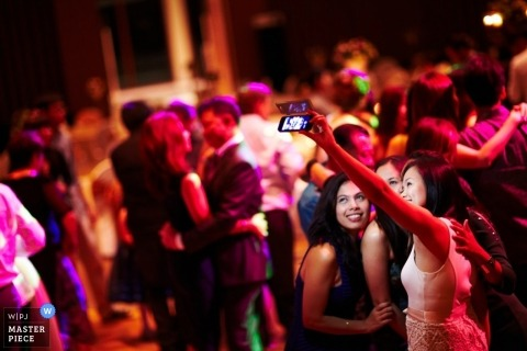 Singapore wedding photographer caught the action of the bride taking selfies on the dancefloor with wedding guest