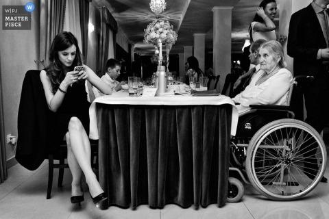 Der Krakauer Hochzeitsfotograf schießt ein Schwarz-Weiß-Bild von Hochzeitsgästen, die an einem langen Banketttisch sitzen