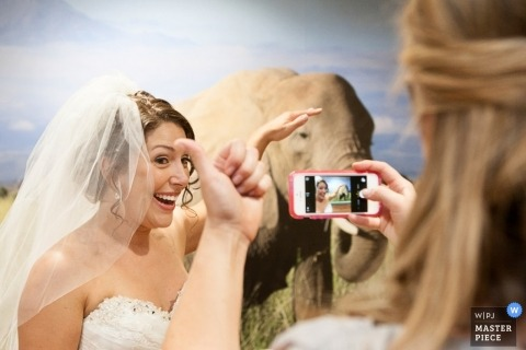 Omaha wedding photographer caught the moment the bride was taking a selfie next to a painting of an elephant before the ceremony