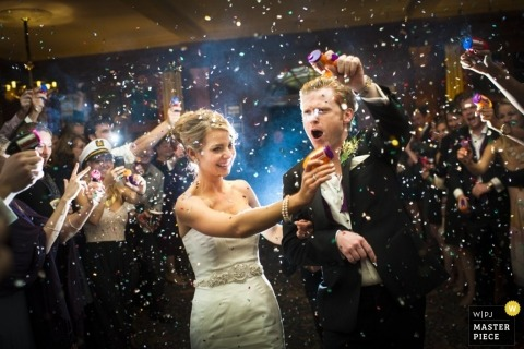 Atlanta wedding photographer freezes the action in this image of the bride and groom leaving the reception as they are showered with confetti
