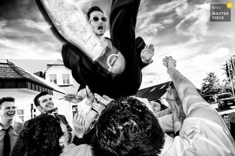Der baden-württembergische Hochzeitsfotograf hat dieses humorvolle Foto des Bräutigams aufgenommen, der während des Hochzeitsempfangs in die Luft geworfen wurde