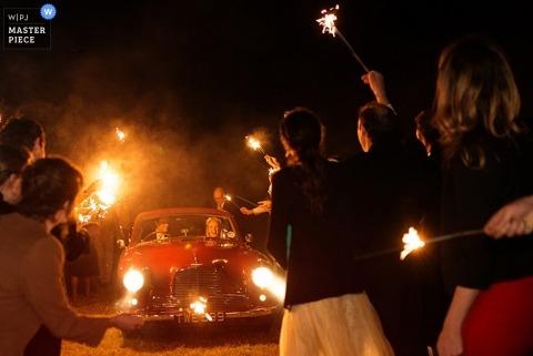 Hampshire-Hochzeitsfotograf entwarf dieses Foto der Gäste, die die Braut und den Bräutigam mit Wunderkerzen in der Dunkelheit wegschicken