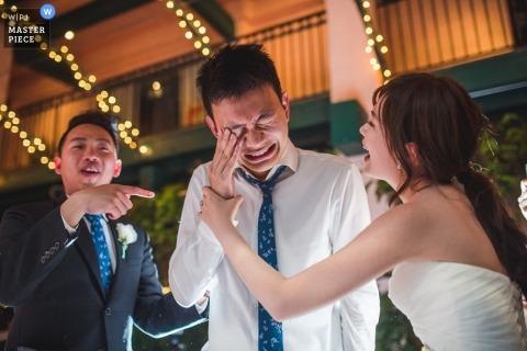 De huwelijksfotograaf in Washington DC maakte deze foto van de bruidegom die iets uit zijn ogen veegde terwijl de bruid en de getuige in de buurt lachen