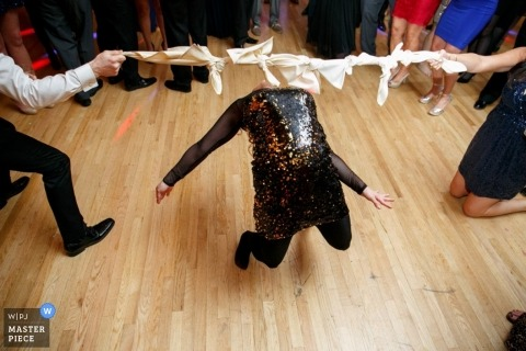 Long Island wedding photographer freezes the action in this image of a wedding guest doing the Limbo on the dance floor