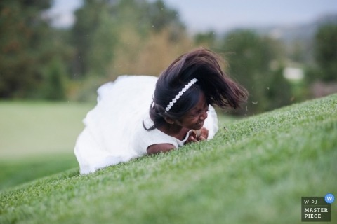 Boulder wedding photographer seized the moment in this image of the flower girl having a great time as she rolled down a grassy hill