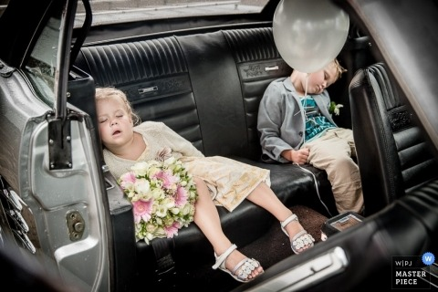 Limburgh-NL wedding photographer creates a picture of two young wedding goers that are taking a nap in the back of the car