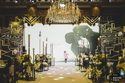 Shanghai wedding photographer creates a picture of a little girl looking up at a big screen of the bride and groom kissing