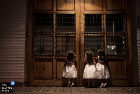 A wedding photographer gets a shot of three little girls looking into a window at the church before the ceremony