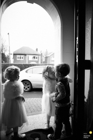 Caught up in the emotion from the ceremony, a little boy and girl kiss at the church door in this photo taken by a Belfast wedding photographer