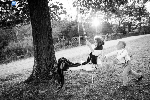 Denver wedding photographer makes a black and white picture of children playing on a swing at the outdoor reception
