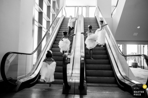 Austin wedding photographer shoots the action of the bridesmaids riding the escalator up and down before the ceremony
