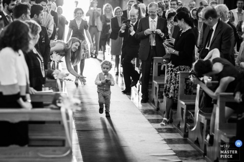 Montana wedding photographer creates a black and white picture of the ring bearer walking down the aisle after getting a little encouragement