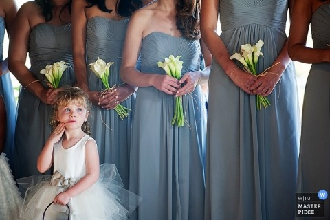 Boulder wedding photographer shoots an image of a little flower girl dressed in white, standing in front of a line of bridesmaids wearing blue