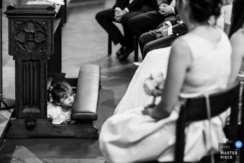 Lower Saxony wedding photographer gets a shot of a little girl relaxing under the alter at church