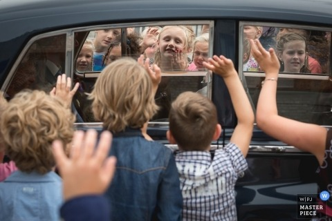 Zuid Holland wedding photographer caught the moment that the bride and groom were being wished farewell by a group of kids after the ceremony