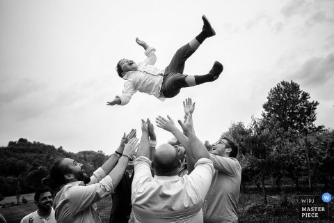 Arezzo wedding photographer shoots the action in this black and white photo of a little boy getting tossed up in the air at the wedding reception