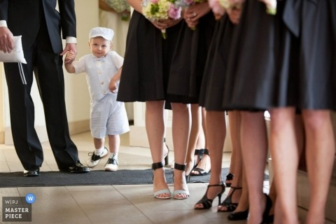 Chicago wedding photographer shoots the moment that the ring bearer gets a little assistance down the aisle