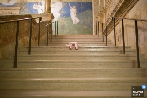 A little girl's legs can be seen as she lays down on a large flight of stairs in this award-winning photo composed by a San Francisco, CA wedding photographer.
