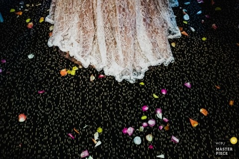 New South Wales, Australia wedding photographer crafted this detail shot of the brides skirt surrounded by flower petals