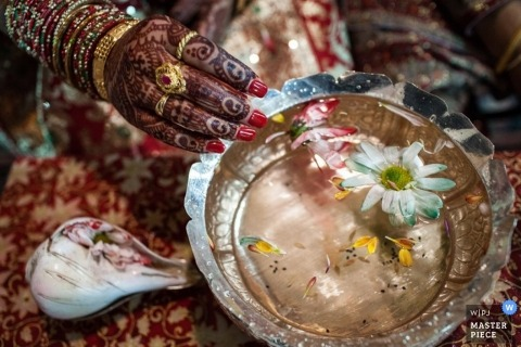 Montana wedding photographer creates this photo of a henna tattooed hand dipping into a bowl of water filled with floating flowers