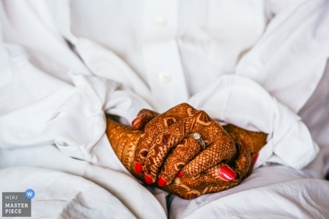 Brussels wedding photographer creates a detail shot of the brides clasped hands that are covered with henna tattoo