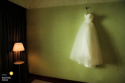 De trouwfotograaf van Lyon maakt een afbeelding van de witte jurk van de bruid die tegen een groene muur hangt