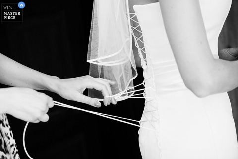 A wedding photographer captured this black and white image of the bride getting her gown laced up before the ceremony