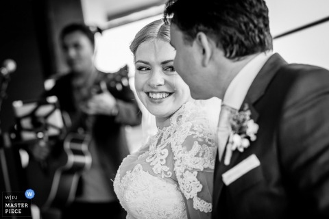 Limburg-NL wedding photographer created this black and white portrait shot of the bride and groom smiling at each other after the ceremony while the band plays in the background