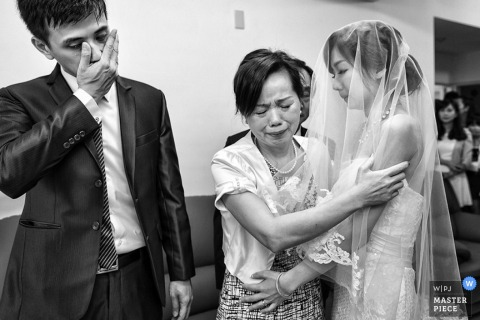 Taipei wedding photographer captured this emotional black and white image of the brides mother giving her a hug after the ceremony