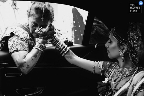 London wedding photographer captured this black and white photo of a bride holding hands with her mother in the car before the wedding ceremony