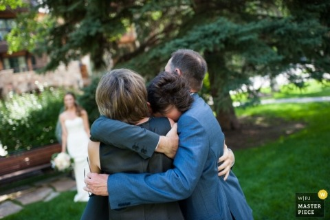 Colorado wedding photographer caught the moment the groom emotionally embraced his parents during the ceremony