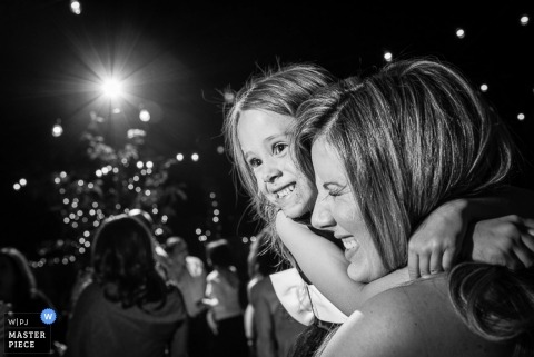 Denver wedding photographer caught the moment of a mother and daughter embracing in this black and white photo at the reception