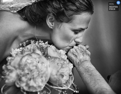 Valencia wedding photographer caught the moment in this emotional black and white photo the bride kissing the hand of her grandmother as a tear ran down her cheek