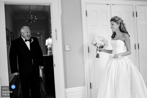 A father exclaims excitedly when he sees his daughter in  her wedding dress in this black and white image created by a Charleston, SC documentary wedding photographer.