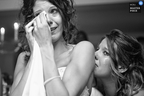 Arezzo wedding photographer shoots the emotional moment of the bride wiping tears with a napkin in this black and white photo