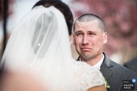 New Jersey wedding photographer shoots the moment of the groom getting emotional as he stands with the bride at the ceremony