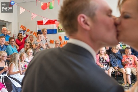 Zuid Holland wedding photographer captured this image of the bride and groom having their first kiss while we can see the wedding guests sitting in the background
