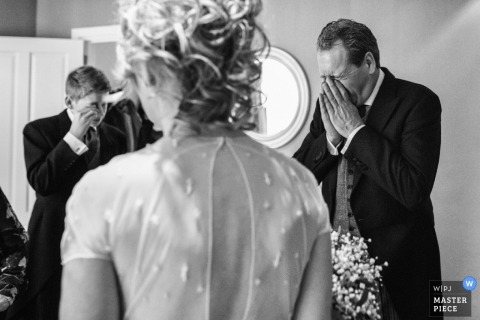 Overijsselwedding photographer captured this emotional black and white photo of the brides father and brother wiping tears from their eyes as they ready to walk her down the aisle