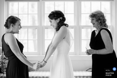 Boston wedding photographer shoots a picture of the bride getting well wishes from her sister and mother before walking down the aisle