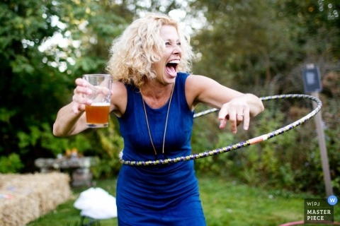 A woman laughs as she hula-hoops while holding her beer in this documentary-style photo by a Providence, RI wedding photographer.