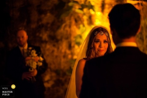 Northern California wedding photographer captured this photo of the bride listening to her groom say his vows in the beautiful golden glow of the chapel